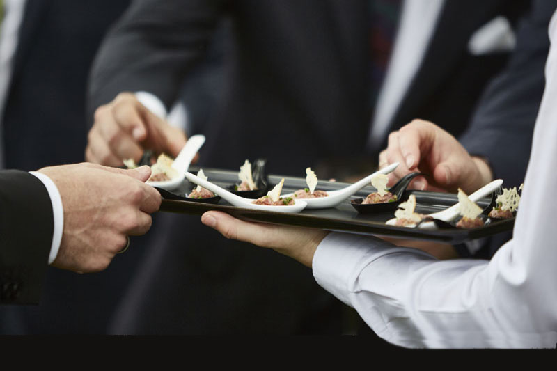 Hands of men taking gourmet appetizers served by professional waiter